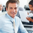 Confident businessman smiling with team in background - Stock Photo