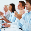 Happy businesspeople applauding on an achievement at work - Stock Photo