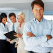 Royalty-Free Stock Photo: Confident business executive with colleagues working at the back