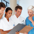 Royalty-Free Stock Photo: Doctor and nurses going through a report