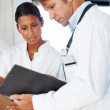 Male and female doctors talking over file - Stock Photo