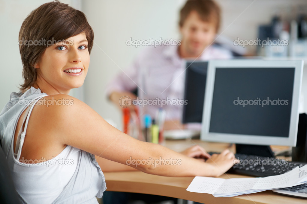 Young business woman working on computer and looking at you — Stock Photo #7781032