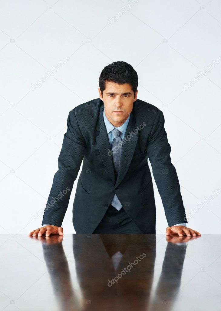 Executive standing and leaning with hands on table — Stock Photo #7783501