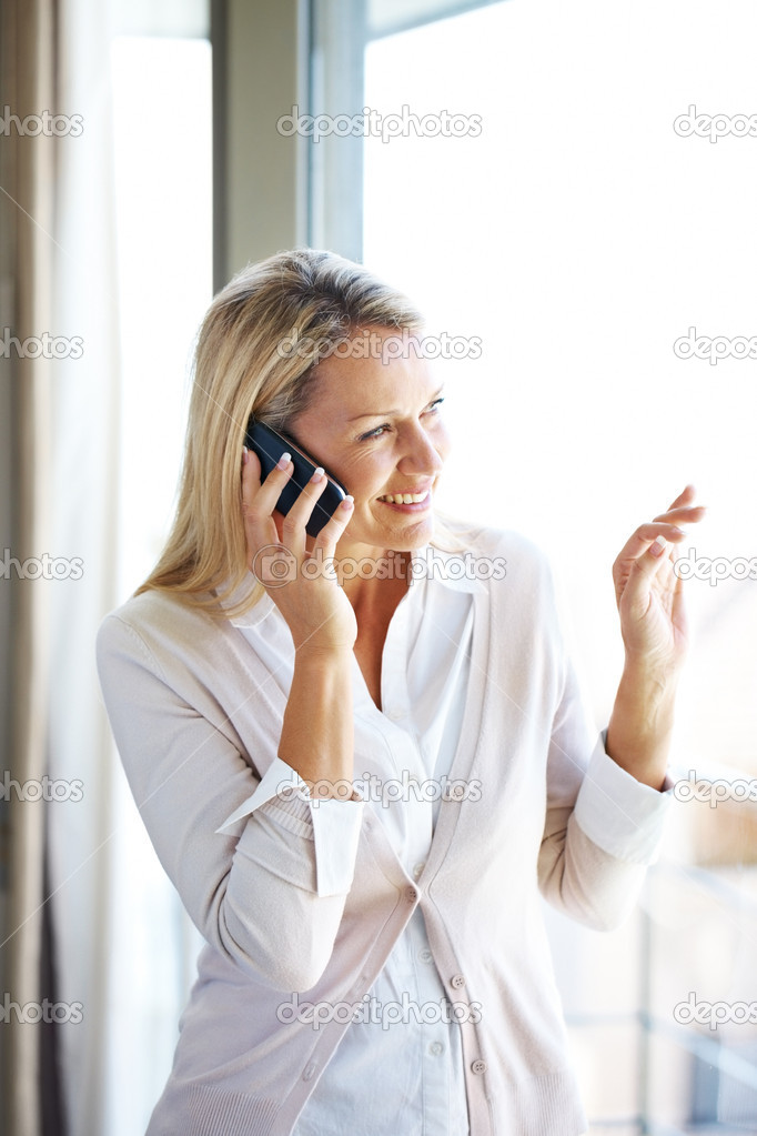 Portrait of a pretty young woman talking on mobile phone and looking away through window -Indoor  Stock Photo #7783552