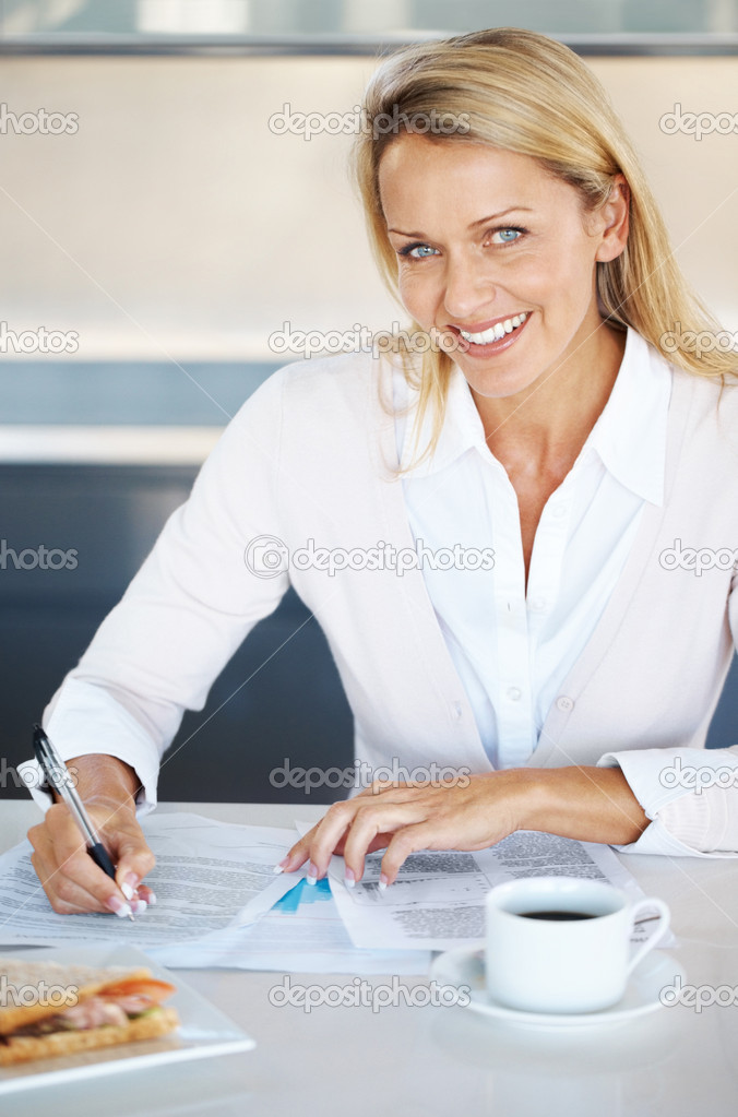 Portrait of a smiling young businesswoman writing something with with cup of coffee — Stock Photo #7783600