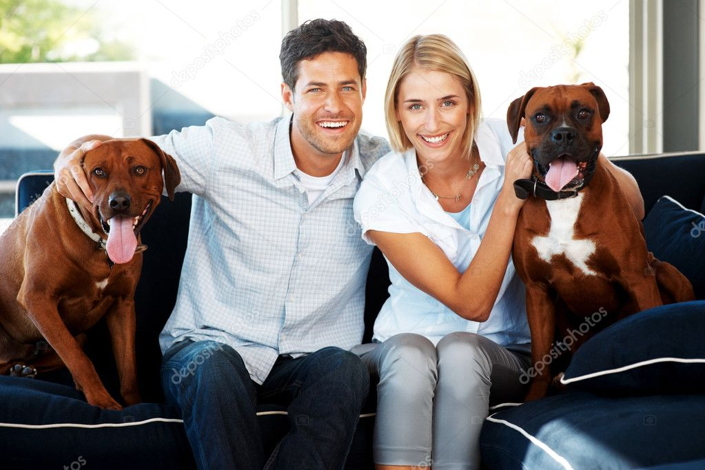 Portrait of a happy young couple sitting on sofa with their dogs at home - Indoor  Foto Stock #7783826