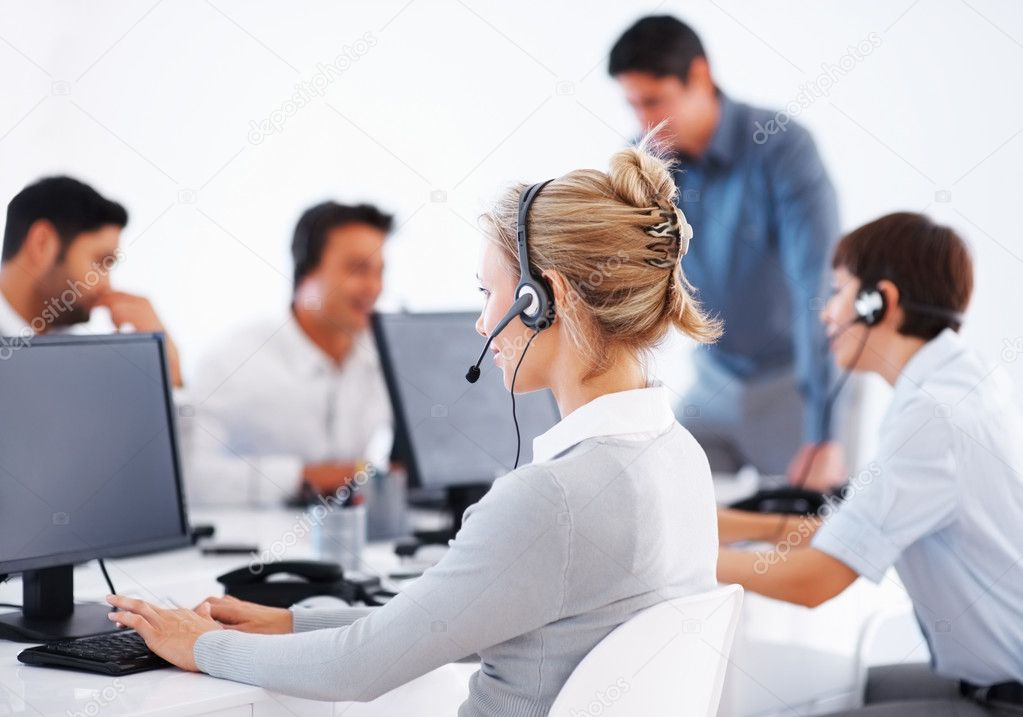 Business woman wearing headset working on computer with colleagues in background — Stock Photo #7787212
