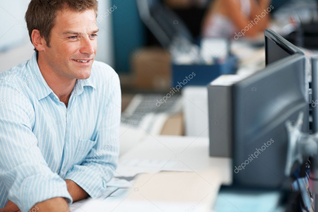 Portrait of a smart young businessman working on computer at office  Stock Photo #7788168