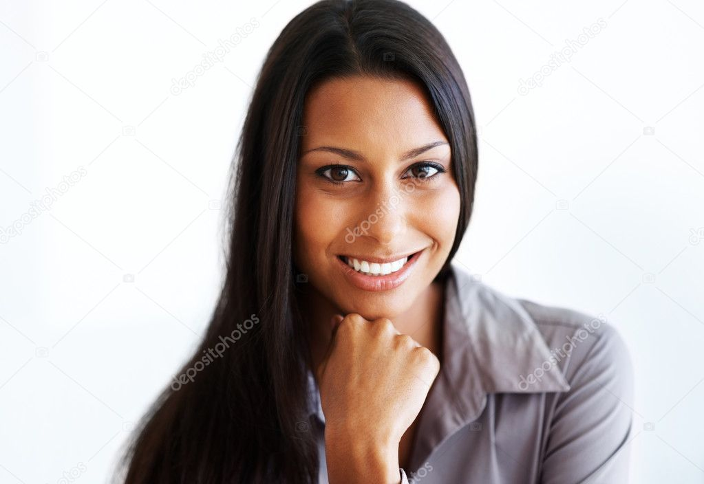Portrait of a smiling young businesswoman with her hand on her chin against white background  Stock Photo #7788246
