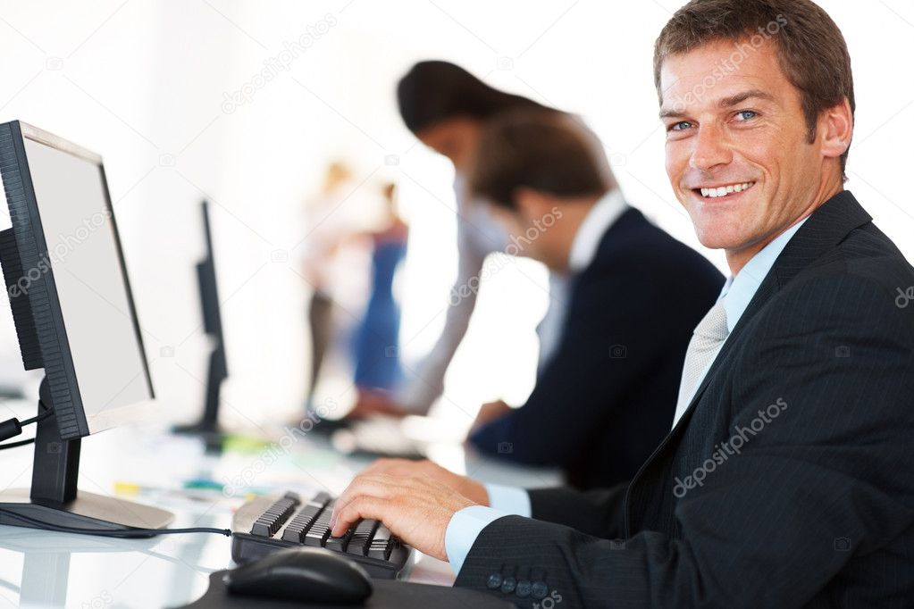 Portrait of a smiling young businessman working on computer at office with his colleagues — Stock Photo #7788271