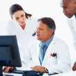 Doctors reviewing medical reports - Stock Photo
