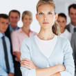 Royalty-Free Stock Photo: Confident young businesswoman with her team in background