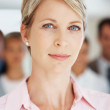 Royalty-Free Stock Photo: Serious business woman with colleagues in background