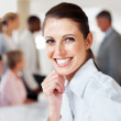 Closeup of pretty executive with colleagues in background - Stock Photo