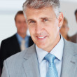 Senior manager smiling and his colleagues standing behind - Stock Photo