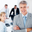 Royalty-Free Stock Photo: Happy senior manager with his team working in background