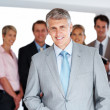 Royalty-Free Stock Photo: Senior manager smiling and his team standing behind