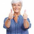 Excited senior lady showing thumbs up against white - Stock Photo