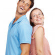 Happy young couple standing back to back - Stock Photo