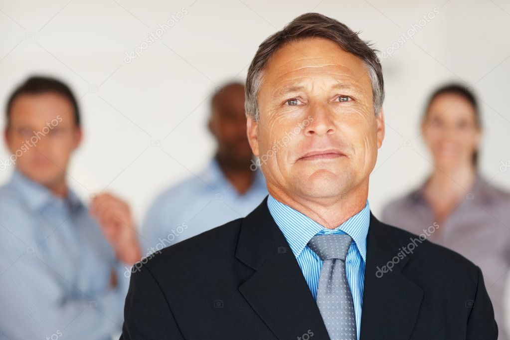 Closeup portrait of confident mature manager with team in background — Stock Photo #7814793