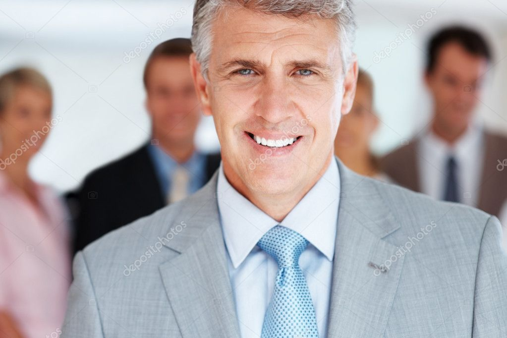 Portrait of a smart mature business manager smiling and his team standing in background  Stock Photo #7815425