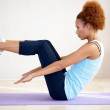 Young beautiful sportswoman exercising on a mat - Stok fotoğraf