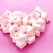 Sweet heart shaped marshmallows on pink background - Stock Photo