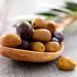 Green arbequinas and dry black empeltre olives on a spoon - Stock Photo