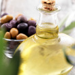 Bottle of olive oil and a bowl with black and green olives - Stock Photo