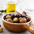 Bowl full of green and dry black olives - Stock Photo