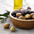 Green and dry black olives in a bowl - Stock Photo