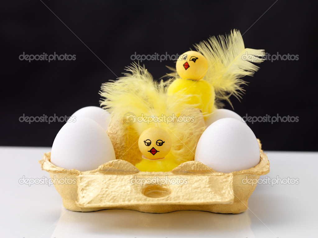 Raw eggs with cute little chicks in a cardboard container against black background — Stock Photo #7839898