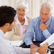 Agent discussing investment plans with a senior couple - Stock Photo