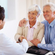 Senior couple shakes hands with their financial advisor - Stock Photo