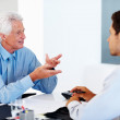 Financial planner discussing investment plans with a man - Stock Photo