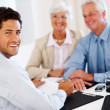 Royalty-Free Stock Photo: Happy male advisor with an old couple in background
