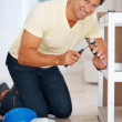 Royalty-Free Stock Photo: Man building shelf and smiling