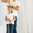 Father measuring daughter's height - Stockfoto