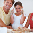 Family baking cookies in kitchen and smiling - Stock Photo