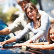 Young girl washing car with sister and father - Stock Photo