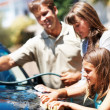 Young girl washing car with family - Stock Photo