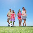 Royalty-Free Stock Photo: Young girl playing football with family on grass