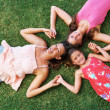 Royalty-Free Stock Photo: Mother and daughters lying on grass with heads together