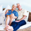 Senior couple sitting on a sofa and smiling - Stok fotoğraf