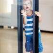 Cute kid looking through glass door - Stock Photo