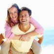 Man giving piggyback ride to woman - Stock Photo