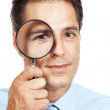 Young businessman looks through a magnifying glass - Stock Photo