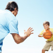 Happy small kid playing basketball with his father - Stok fotoğraf