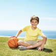 Cute little boy sitting on grass with a basketball - Stock Photo