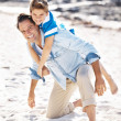 Royalty-Free Stock Photo: Happy father piggybacking his cute son at the beach